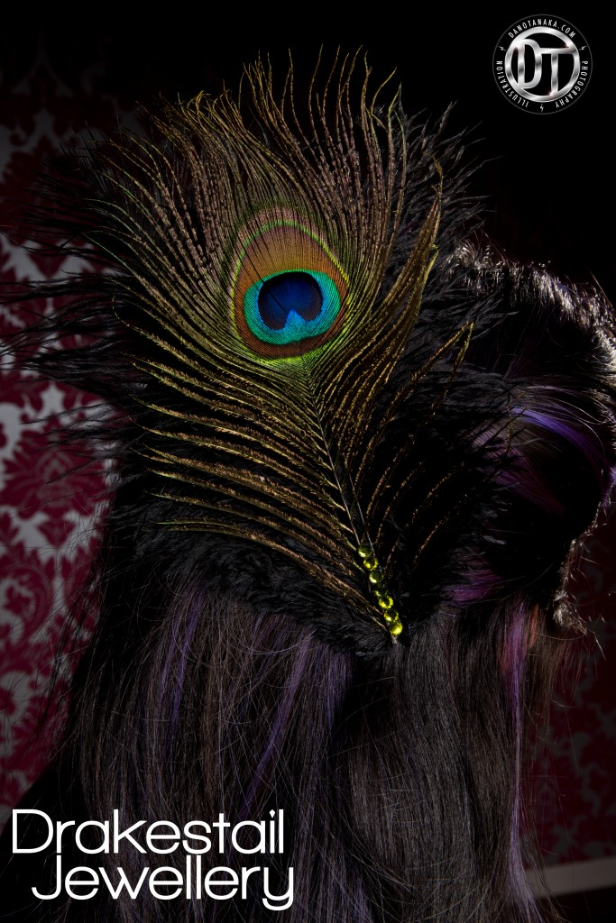 Ostrich and peacock feather fascinator with green crystal ornamentation.
